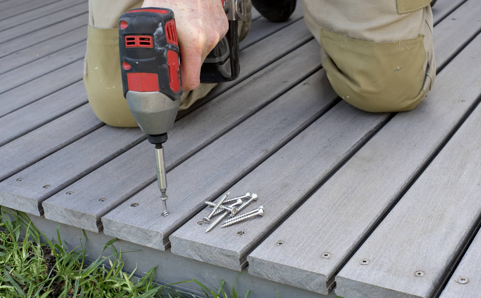An image of a deck contractor screwing in boards for a new deck.